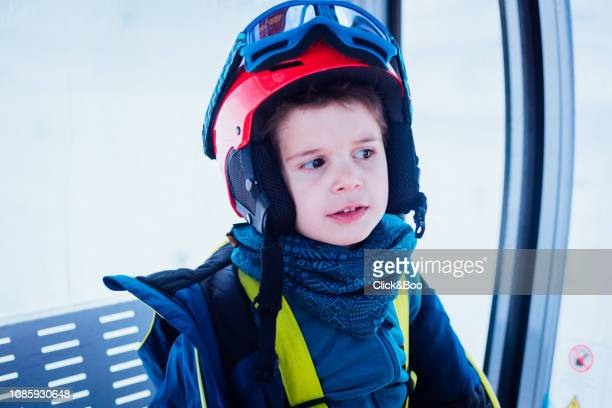 Little boy dressed in ski clothes learning to ski