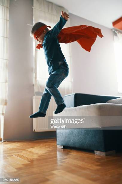 little boy dressed up as a superhero playing at home - cape garment stock photos and pictures