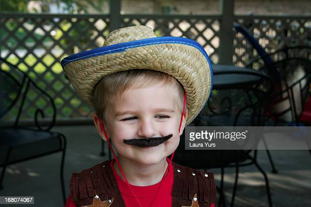 little boy dressed up as cowboy with mustache