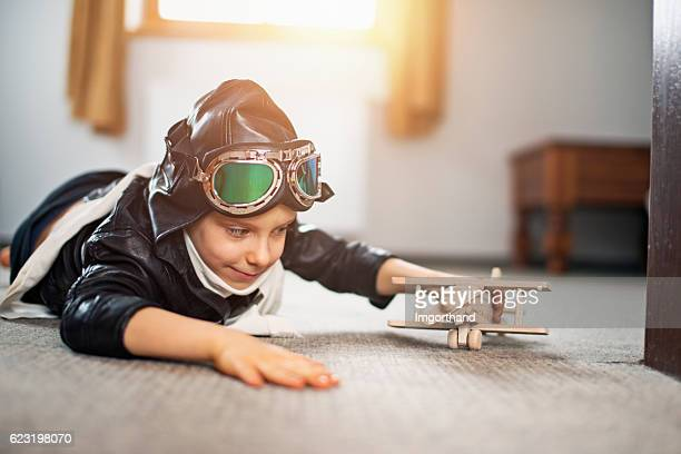 little boy dressed up as pilot playing with toy plane - tapijt stockfoto's en -beelden