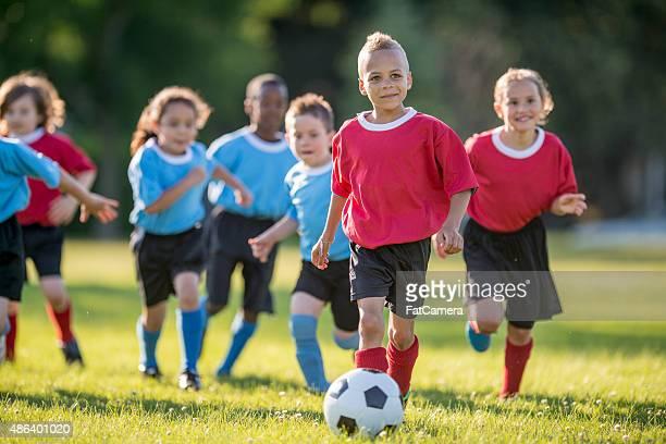 Little Boy Dribbling a Soccer Ball
