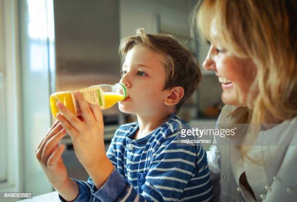 little  boy drinking fresh orange juice. - juice drink stock photos and pictures
