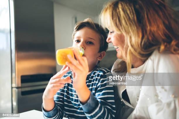Kleiner Junge, frischen gepressten Orangensaft trinken.