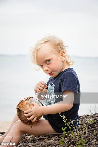 Little boy (3-4) drinking from coconut