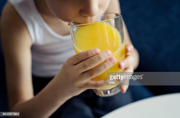 little boy drinking orange juice - orange juice stock pictures, royalty-free photos & images