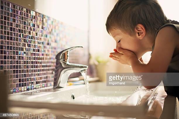Rapaz beber água da torneira
