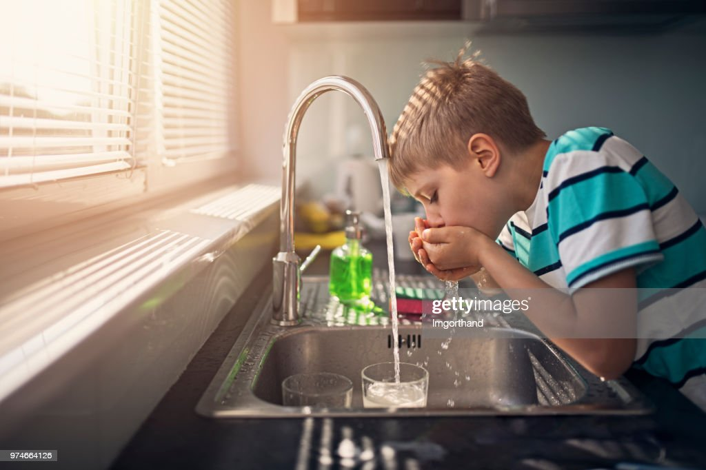 Little boy drinking tap water : Stock Photo