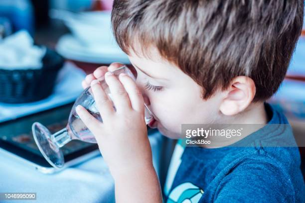Little boy drinking water from a glass (indoors)