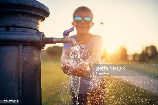 little boy drinking water from public fountain - fountain stock pictures, royalty-free photos & images