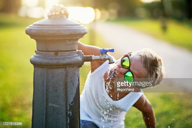 little boy drinking water from public fountain - thirsty stock pictures, royalty-free photos & images