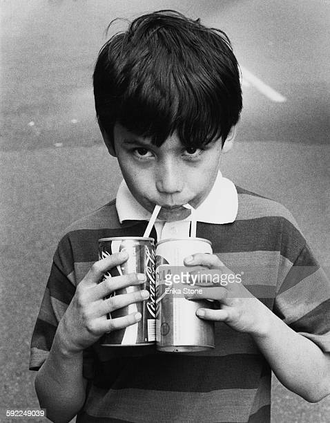Little boy drinks a can of Coca-Cola and a can of Pepsi-Cola simultaneously in New York City, USA, circa 1978.