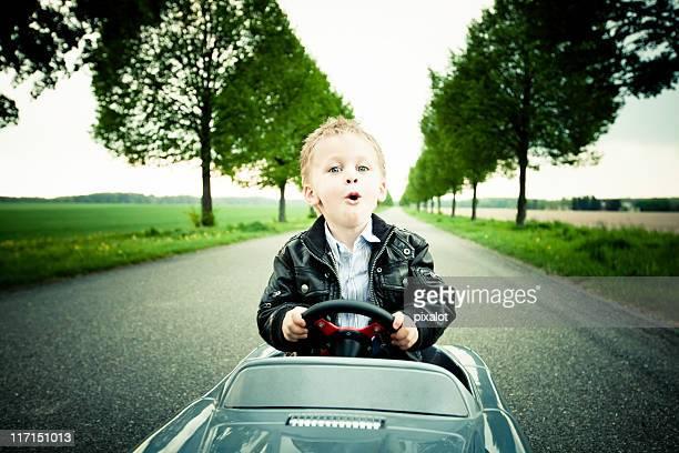 Kleiner Junge mit Spielzeugauto fahren