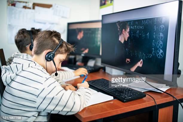 little boy during covid-19 quarantine attending to online school class. - remote location stock pictures, royalty-free photos & images