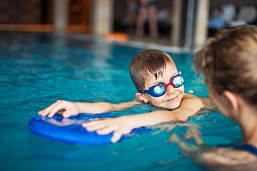 Little boy during swimming lesson at indoors swimming pool 625735914