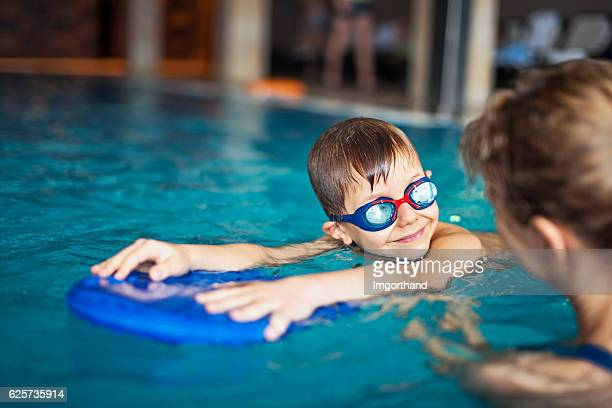 little boy during swimming lesson at indoors swimming pool - auf dem wasser treiben stock-fotos und bilder