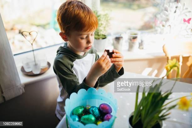 チョコレート イースターの卵を食べる少年 - イースターエッグのチョコレート ストックフォトと画像