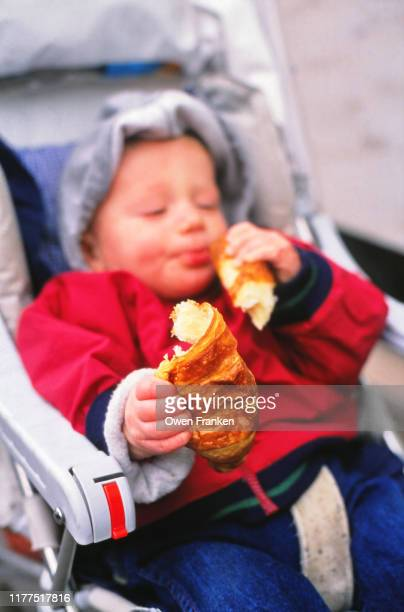 little boy eating a french croissant - image photos et images de collection