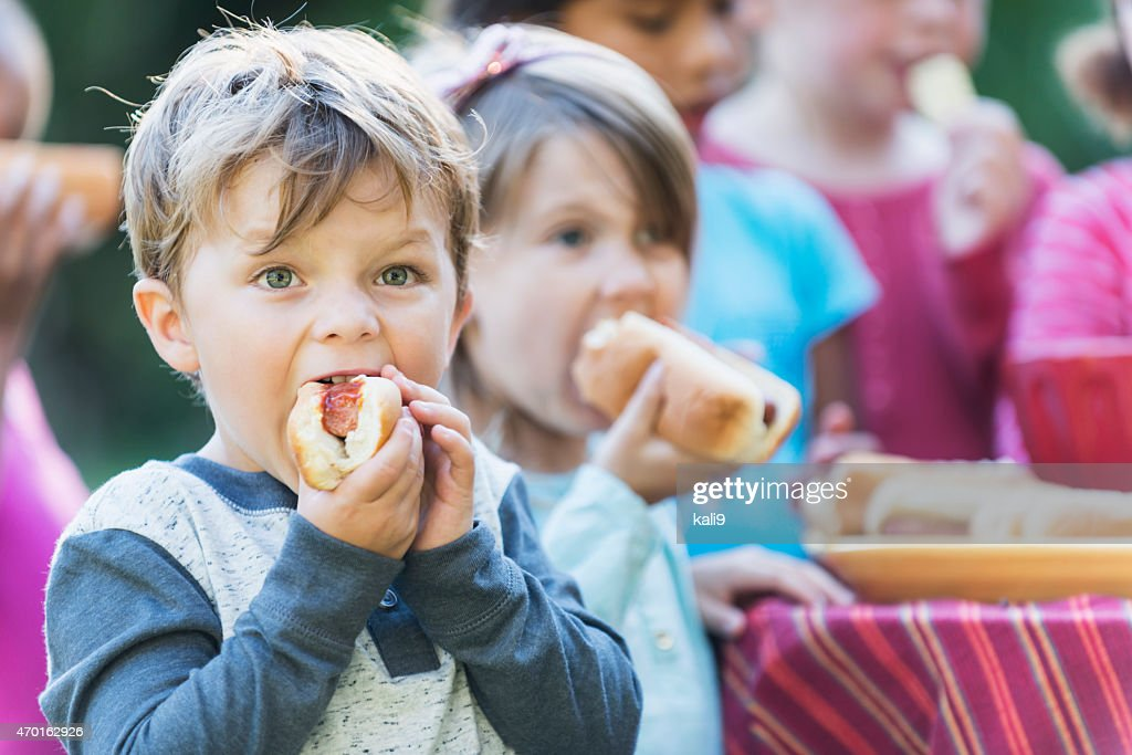 Little boy eating a hotdog at a cookout : Stock Photo