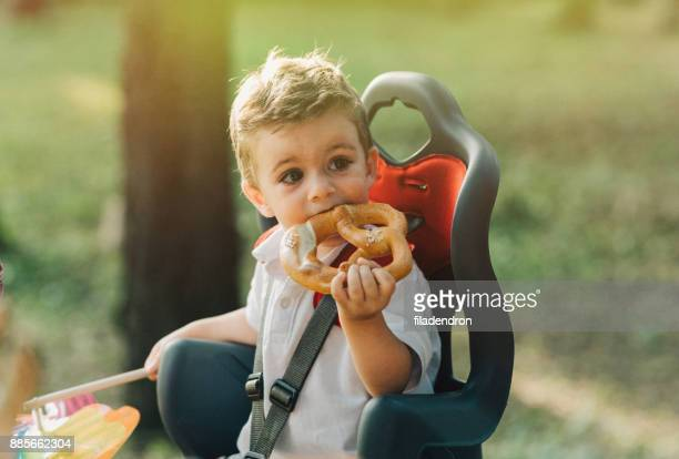 Little boy eating a pretzel in a child seat on a bicycle.