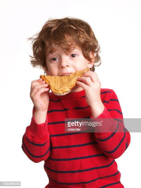 Little boy eating a slice of bread covered in peanut butter