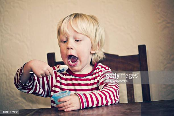 Little boy eating a yoghurt