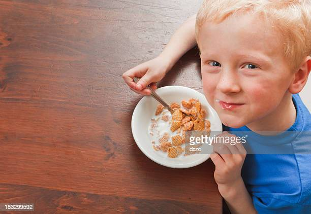little boy eating breakfast cereal