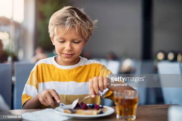 kleine jongen eten ontbijt pannenkoeken met fruit - social grace stockfoto's en -beelden
