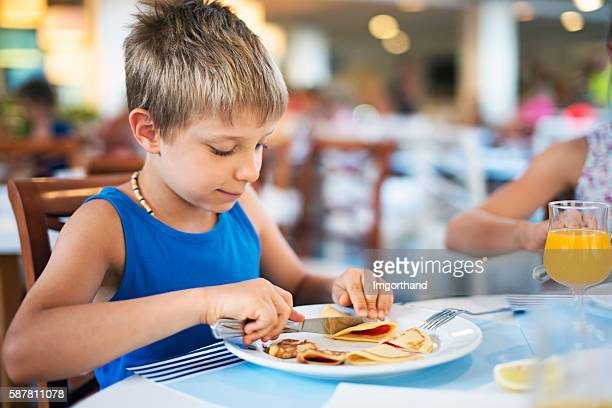 Little boy eating breakfast pakcakes