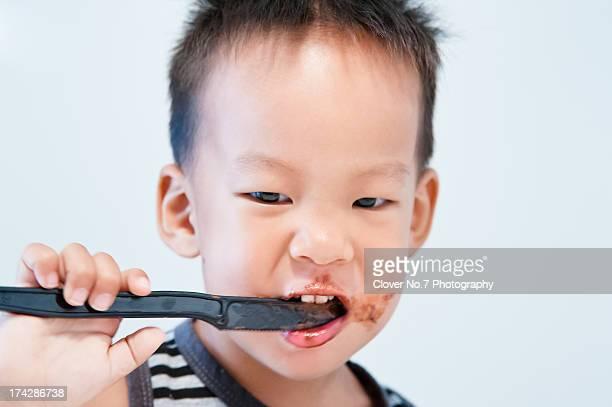 Little boy eating chocolate sauce.