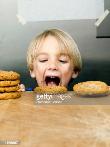 Little Boy Eating Cookies Off Of A Table Stock Photo