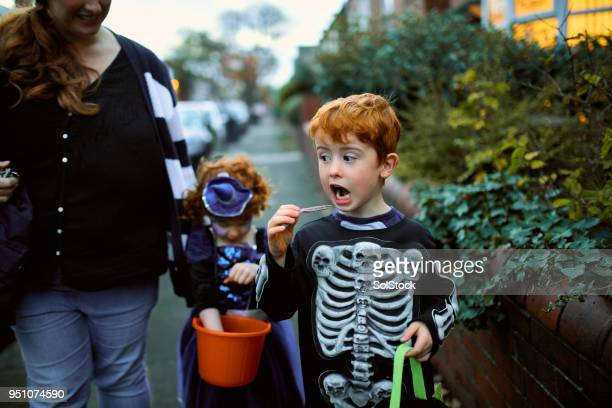 little boy eating halloween candy - halloween candy stock photos and pictures