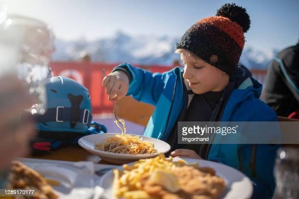 petit garçon mangeant le déjeuner dans le restaurant alpin de ski - sport d'hiver photos et images de collection