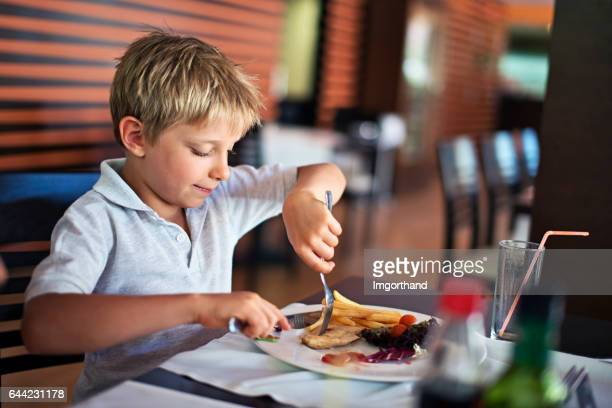 Little boy eating lunch in restaurant