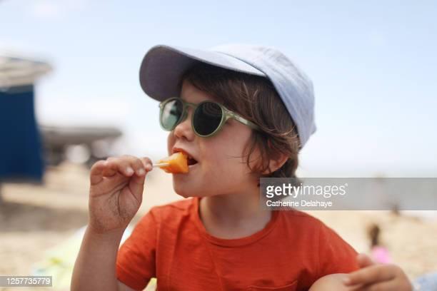 a little boy eating melon on the beach - サングラス ストックフォトと画像