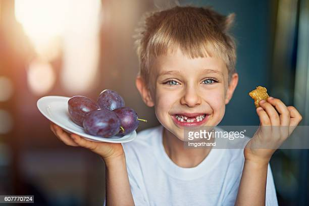 little boy eating plums at home - ciruela fotografías e imágenes de stock