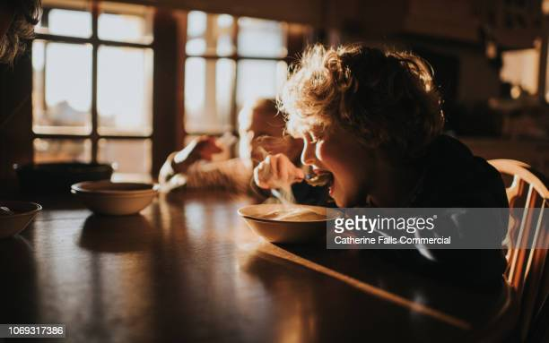 little boy eating pudding - soup stock pictures, royalty-free photos & images