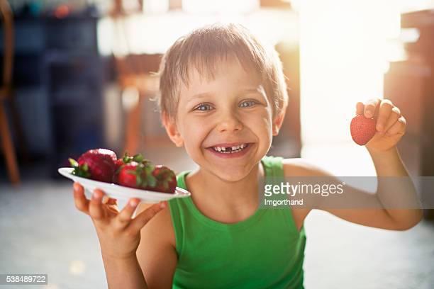 Kleine Junge Essen Erdbeeren wie zu Hause fühlen.