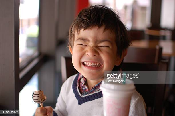 little boy eating sweets and making funny face - v neck stock photos and pictures