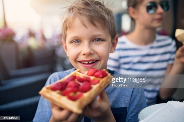 little boy eating waffle with strawberries - waffle stock photos and pictures
