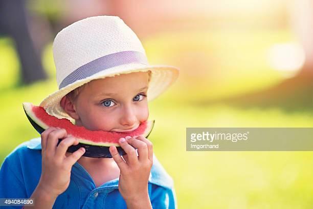 Little boy eating watermelon outdoors