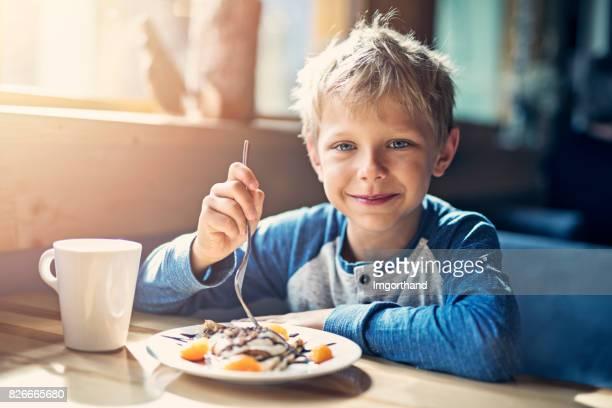 Kleine Junge Ejoying Crepe und Tasse Kakao Frühstück