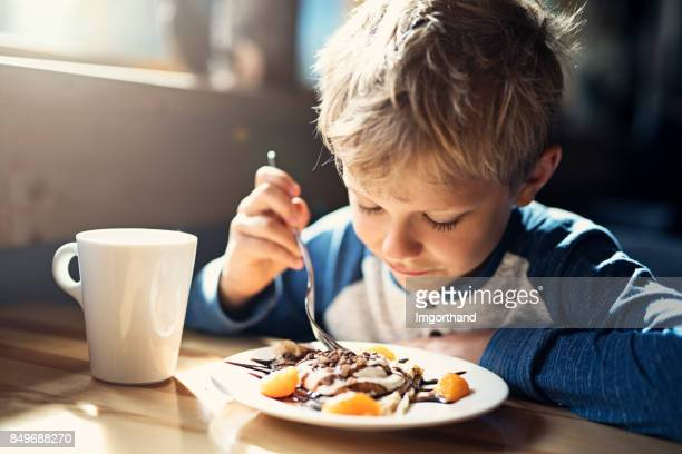 little boy ejoying crepe and cup of cocoa breakfast - pancake stock pictures, royalty-free photos & images