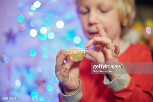 Little boy enjoying a mince pie at Christmas