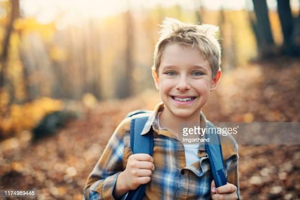 kleine jongen genieten van herfst bos - alleen één jongen stockfoto's en -beelden