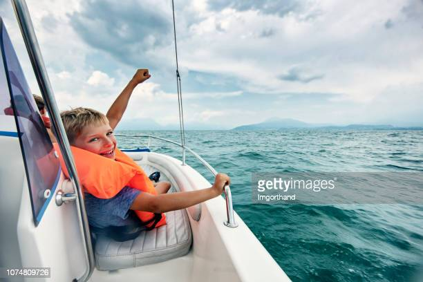 little boy enjoying boat ride on lake garda - nautical vessel stock pictures, royalty-free photos & images
