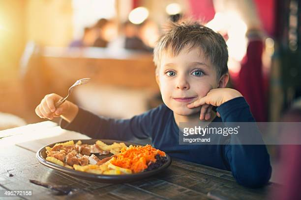 Little boy enjoying dinner at the restaurant
