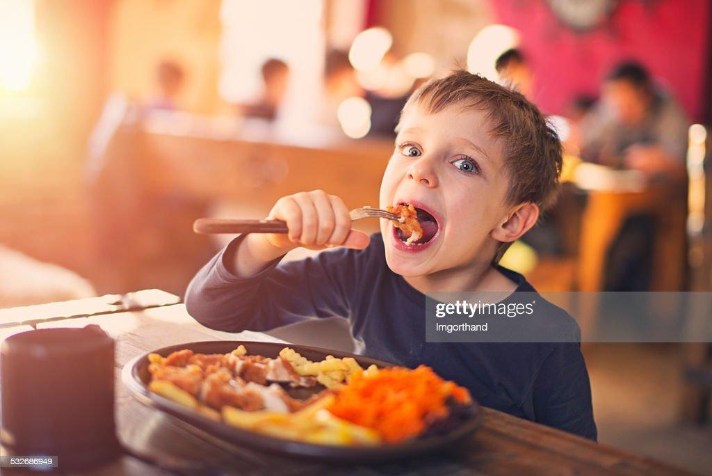 Little boy enjoying dinner at the restaurant