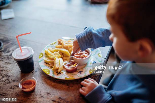 Little Boy Enjoying Fish and Chips at a Beach Cafe
