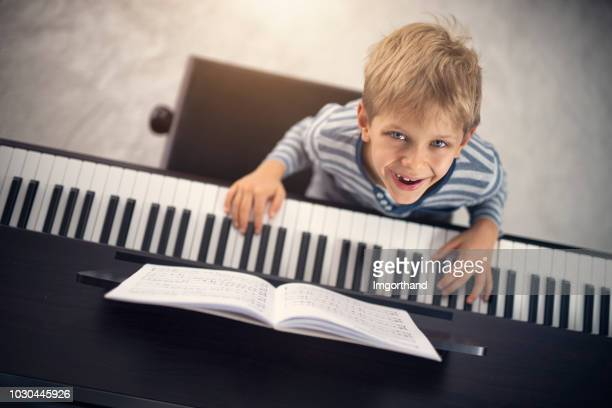 little boy enjoying learning piano - electric piano stock photos and pictures