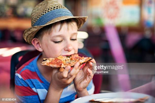 Little boy enjoying pizza in restaurant